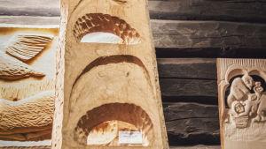 Erilaisia puusta veistettyjä reliefejä.