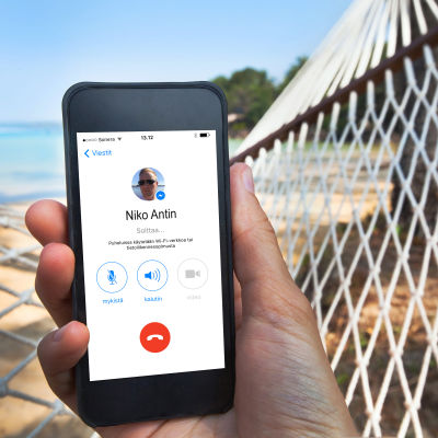 Käsi joka pitelee älypuhelinta riippukeinussa rannalla.