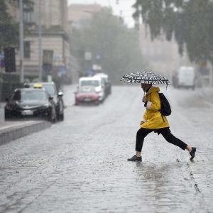 Två personer korsar gatan åt olika håll, med stora hoppande steg och paraply i händerna. Det ösregnar och gatan är nästan översvämmad.