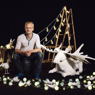 En man som sitter med låtsasdjur och ser in i kameran