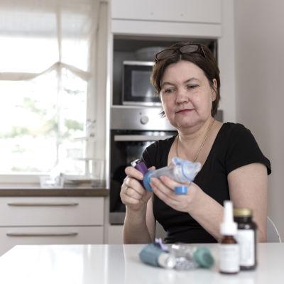 Tammilehto keittiön pöydän ääressä katselee lääkkeitään.