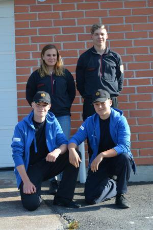 Fyra brandkårister ler mot kameran.