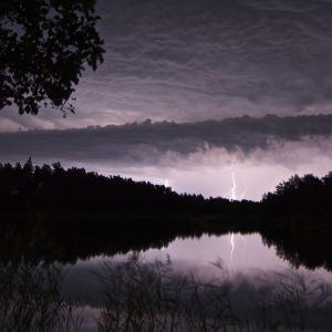 Blixt slår ner i fjärran, i förgrunden spegelblankt vatten och träd.