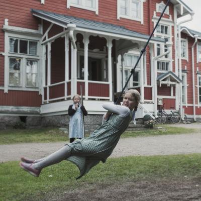 Lapset pyörivät tolppaa ympäri narujen varassa. Taka-alalla tyttö puujaloilla.