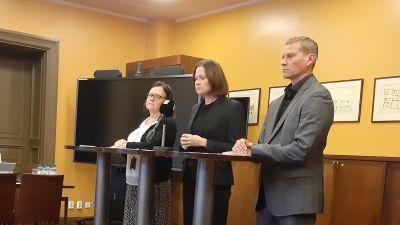 Riitta Liuksa, Minna Arve och Tuomas Heikkinen, tre tjänstemän i Åbo, står allvarliga bakom tre höga bord på en presskonferens.