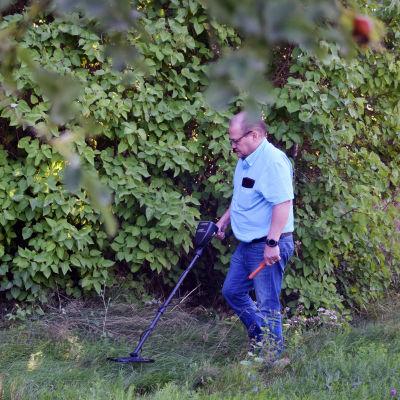 En man går omkring med en metalldetektor vid en hög syrenhäck.