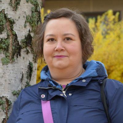 Riikka Laine står bredvid en björk och ler in i kameran. Höstlöv i bakgrunden.