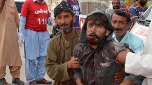 Människor hjälper skadade personer efter ett självmordsdåd i Pakistan.