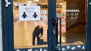 Skylt som uppmanar kunder att hålla två meters avstånd till varandra på dörren till köttsalen i Balti Jaama Turg i Tallinn.