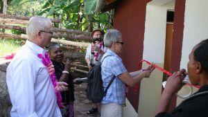 En kvinna med kort grått hår klipper av ett rött band i samband med invigning av en byggnad. Några män står bredvid och följer med, Det är i Afrika, i Tanzania.
