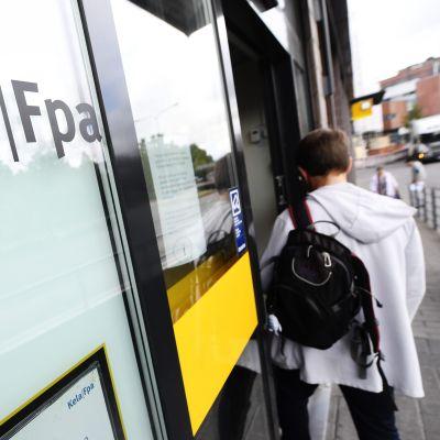 En person med kort hår och ryggsäck går in genom dörren till FPA:s kontor.