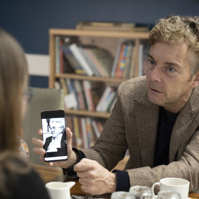 Melcher de Wind , kirjailian poika ,pitelee kännykkää jossa isän kuva