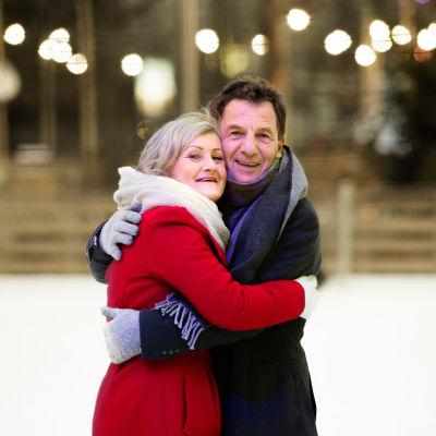 Kvinna i röd kappa kramar om man i svart jacka