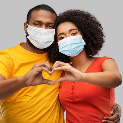 Man och kvinna, båda med munskydd, lutar sig mot varandra och formar ett hjärta med fingrarna