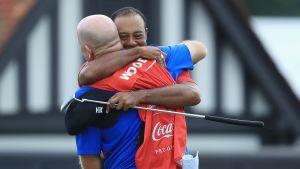 Tiger Woods omfamnar sin caddie Joe LaCava.