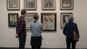 Helene Schjerfbeck-utställning på Ateneum. Tre personer med ryggen mot kameran kollar på tavlor.