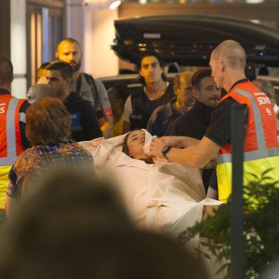 En ung kvinna på bår omhändertas av ambulanspersonal.