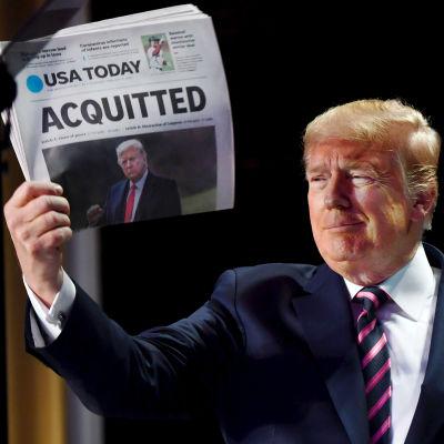 """Donald Trump tittar och sidan och småler medan han håller upp en papperstidning med rubriken """"frikänd"""" tillsammans med en bild på honom."""