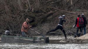 En grupp migranter som lyckades ta sig över gränsfloden Evros hoppade i land på grekisk mark på söndagen.