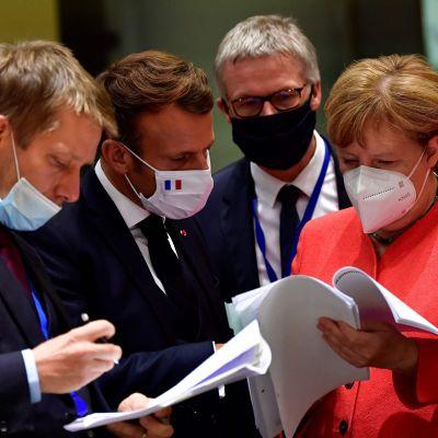 EU-ledare som bär ansiktsskydd tittar igenom dokument som Angela Merkel håller i. På bilden finns bland annat Frankrikes president Emmanuel Macron och Spaniens premiärminister Pedro Sánchez.
