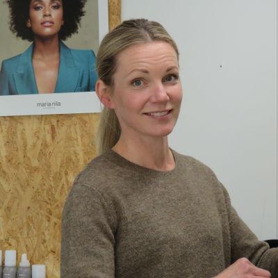 En kvinna med långt ljust hår uppsatt i hästsvans står i en frisörsalong. Hon håller  på med en kund, men ser upp mot kameran och ler lite.