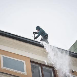 En snöskottare på ett tak i Berghäll i Helsingfors tisdagen den 29.1.2019.