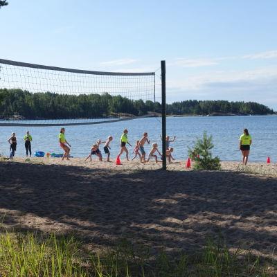 Simskoledeltagare leker på stranden med en volleybollsplan i förgrunden.