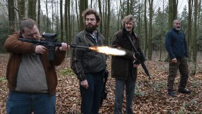 Otto (Nikolaj Lie Kaas), Markus (Mads Mikkelsen), Emmenthaler (Nicolas Bro) och Lennart (Lars Brygmann) står ute i skogen och ser på då Emmenthaler skjuter med automatvapen. sitter i en bil och ser allvarliga ut.
