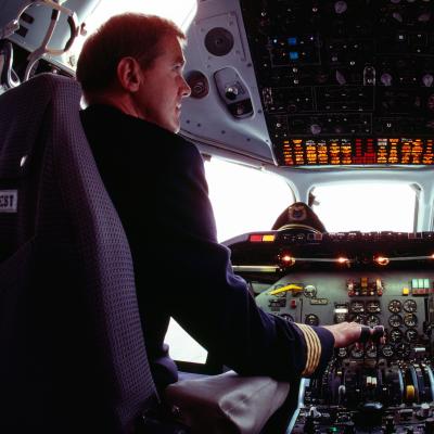 Två piloter sitter i ett flygplan vid styrpanelen. De tittar på varandra medan de sitter på varsin stol.