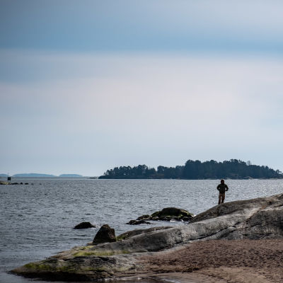 Mies seisoo rantakalliolla Aurinkolahden rannalla.