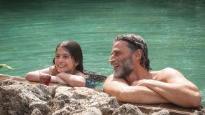 Mies ja nainen ovat vedessä ja nojaavat rantakallioon.