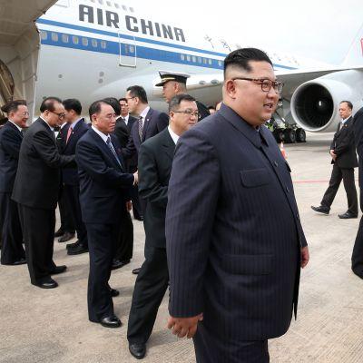 Nordkoreas ledare Kim Jong-Un med följe, efter att de landat på flygplatsen i Singapore.
