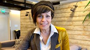 Nainen ruskeissa lyhyissä hiuksissa ja ruskeassa myssyssä katsoo kameraan hymyillen. Taustalla lautaseinä ja toimistonäkymää.