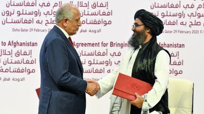 Khalilzad ja Baradar kättelevät. Khalilzadilla on tummansininen puku ja viininpunainen kravatti. Baradarilla on musta turbaani ja perinteinen asu. Hänellä on hieman harmaantunut parta ja silmälasit.