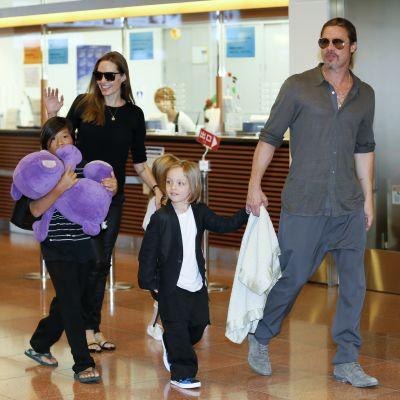 Brad Pitt ja Angelina Jolie kävelevät kolmen lapsensa kanssa lentokentällä.