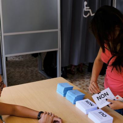 Kvinna lämnar sin valsedel i Noumea i Nya Kaledonien