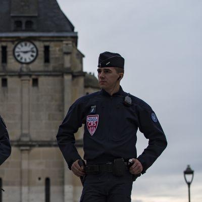 Kaksi poliisia seisoo kirkon edessä. Toinen pitää kädessään rynnäkkökivääriä.