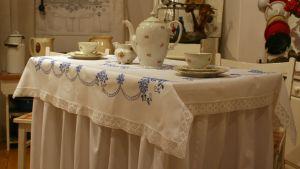 Närbild på ett bord dukat med kaffeservis och en bordsduk som sträcker sig ända ner till golvet.