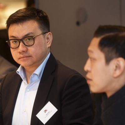 Tre affärsmän sitter vid ett bord. Presskonferens i Helsingfors den 7 december med företrädare för det konsortium som vill köpa Amer Sports aktier.