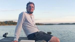 Fredrik Sonck sitter på en somrig brygga