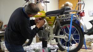 En man reparerar en mooped som står på ett bord i en verkstad. Bakom mopeden kan man skymta några unga pojkar.