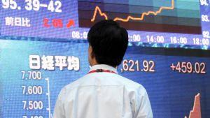 En förbipasserande tittar på börskurserna i centrum av Tokyo