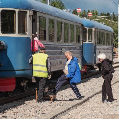 Ihmisiä jonottamassa siniseen junavaunuun.