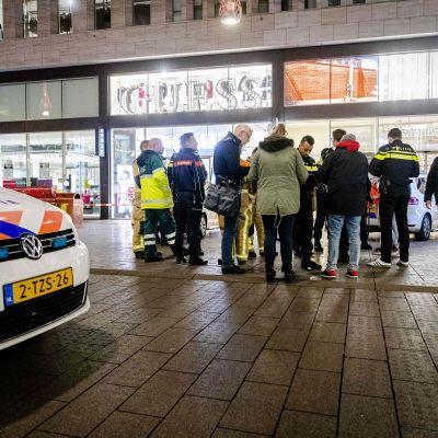 Till vänster en polisbil, till höger en grupp människor.