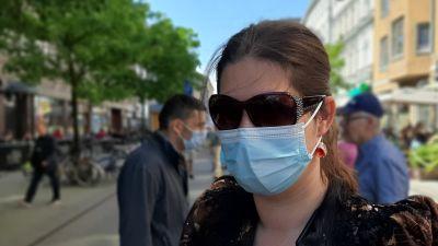Katja Hedman, en dam med långt mörkt hår i hästsvans, solglasögon och ljusblått munskydd, står på en gågata en solig sommardag.