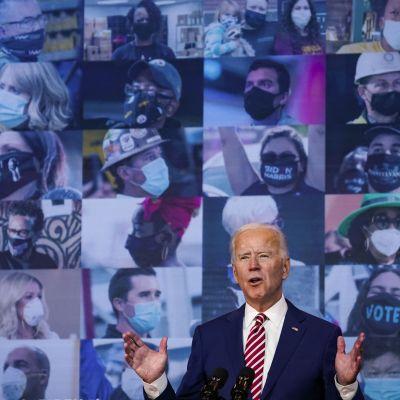 Joe Biden vid mikrofoner, framför en bildvägg med angängare iklädda coronaskydd.