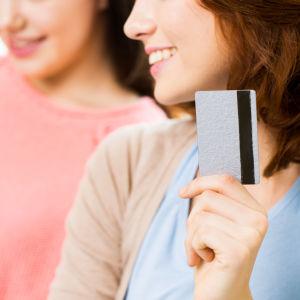 leende kvinna håller upp kreditkort