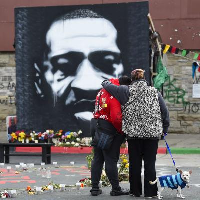 Två personer står med ryggen mot kameran och håller om varandra. de står framför ett enromt svartvitt porträtt av George Floyd. Det finns en massa blommor under porträttet.