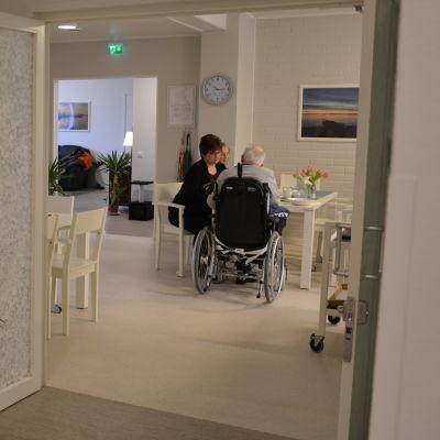 Äldre personer och vårdare vid matbord på avstånd.