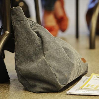 Koululaukku ja kirja luokan lattialla, pulpetin vieressä